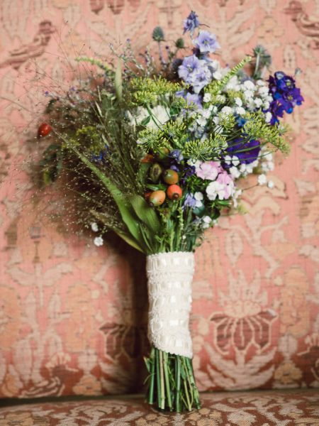 Bouquet of rustic wild meadow and hedgerow flowers sat on dusky coral damask chair