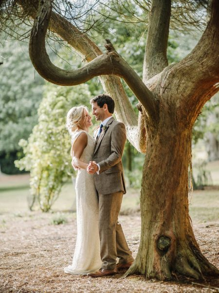 Bride and Groom in brown tweed suit happily dancing under a beautiful yew tree in Studland Bay Dorset