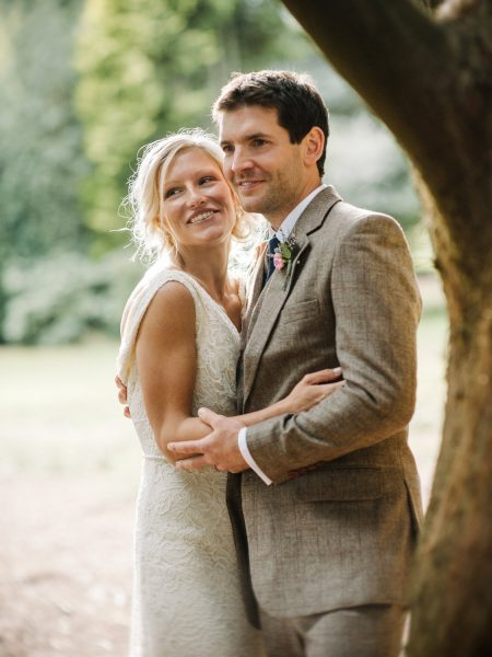 Fine art portrait of a three quarter length Bride and Groom in brown tweed suit smiling happily as they dance under a beautiful yew tree in Studland Bay Dorset