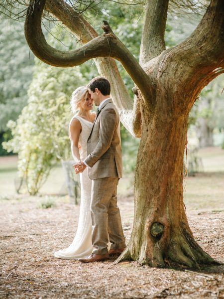 Bride and Groom in brown tweed suit happily dancing touching heads under a beautiful yew tree in Studland Bay Dorset