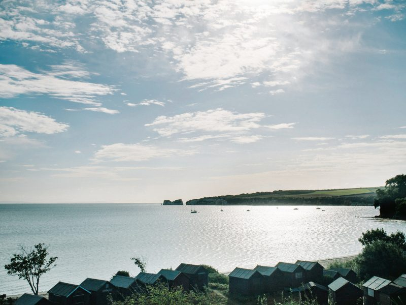 Lanscape scene of sea, Severn needles rock formation, beach huts and clouds Studland Bay Dorset
