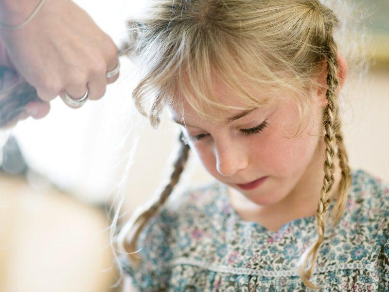 Flower girl head shot of little girl in floral dress having hair braided Studland Bay Dorset