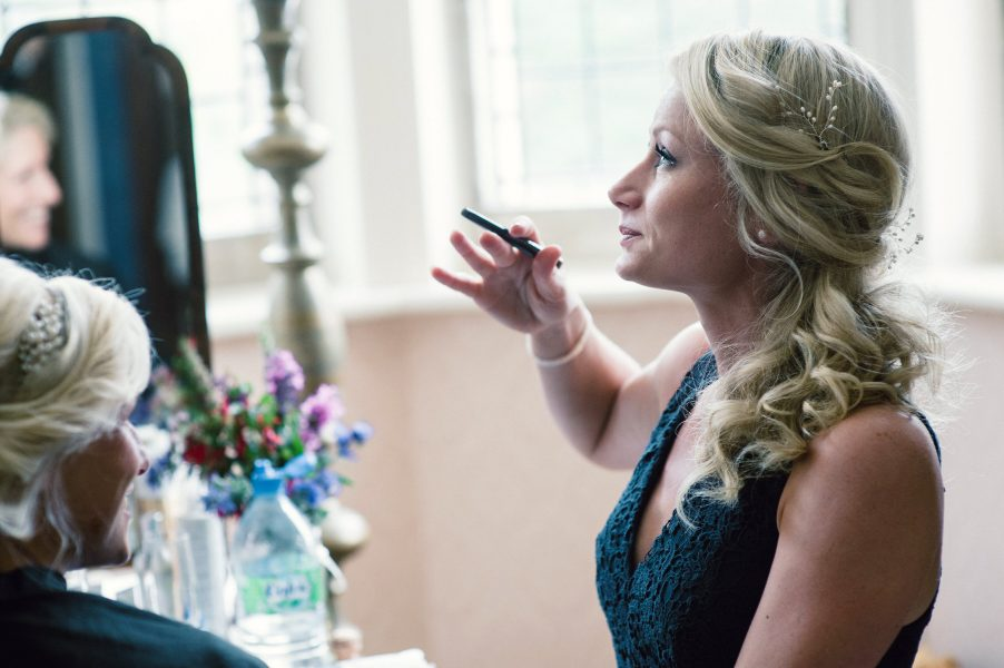 Emotional Bridesmaid with happy tears in her eyes looking up with make up brush in hand in bedroom at Studland House Bay Dorset
