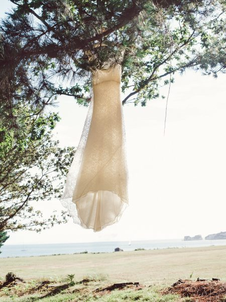 Charlie Brear wedding dress suspended in pie tree with Severn Needles rocks and sea in background Studland Bay Dorset