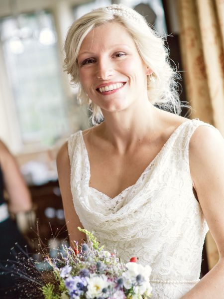 Natural portrait of Bride smiling holding bouquet of rustic wild meadow and hedgerow flowers