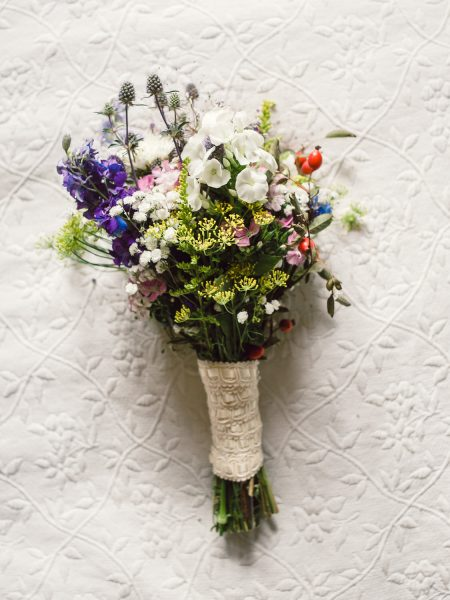Bouquet of rustic wild meadow and hedgerow flowers sat on cream fabric Studland Bay Dorset