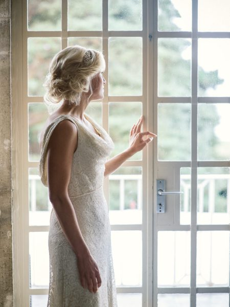 Bride gazes out of window just before she walks to outdoor ceremony Studland Bay Dorset