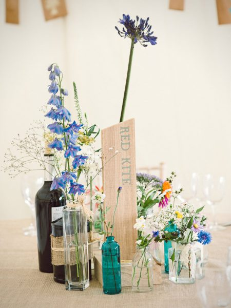 Rustic marquee wild meadow wedding flowers in individual single stem bottles on burlap tablecloth Studland Bay Dorset
