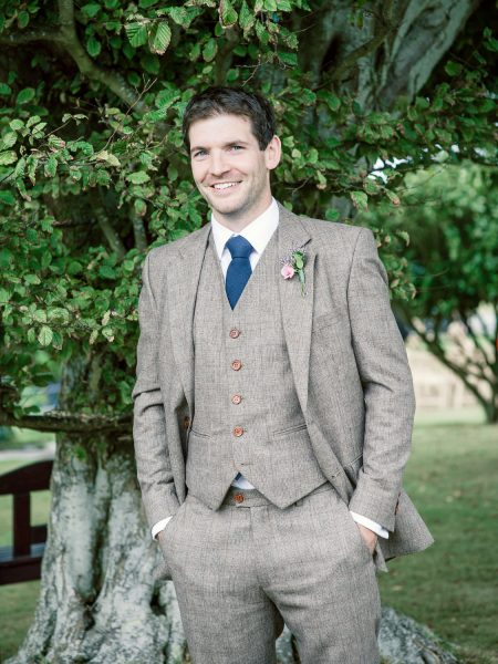 Portrait of smiling Groom in brown three piece tweed suit and blue tie Studland Bay Dorset