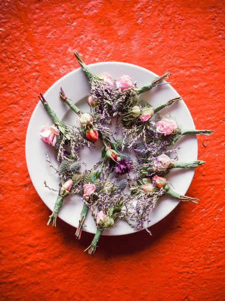Wild meadow rustic wedding buttonholes in a red background