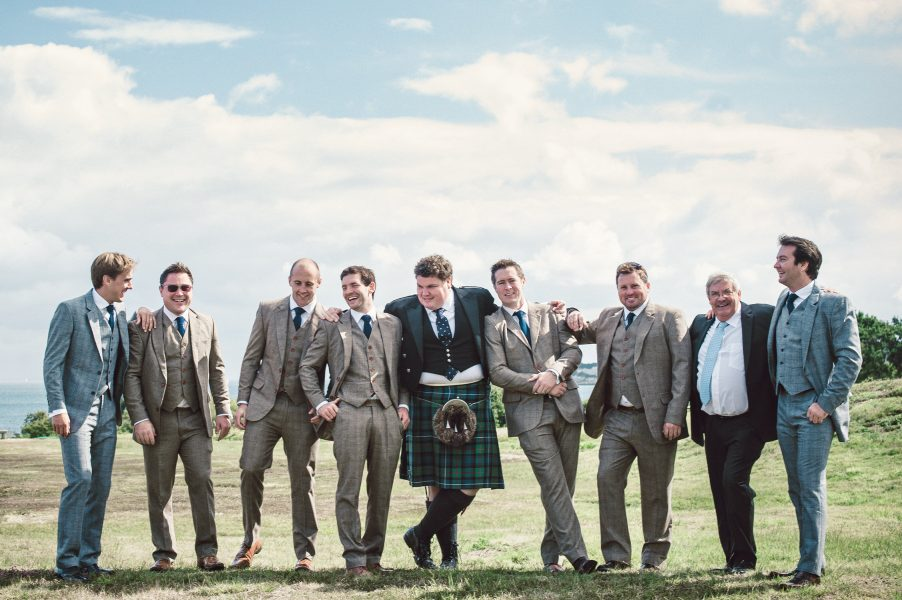 Relaxed fun full length portrait Groom Best Man and Ushers in tweed suits and a kilt with Studland Bay sea coastline in background Dorset