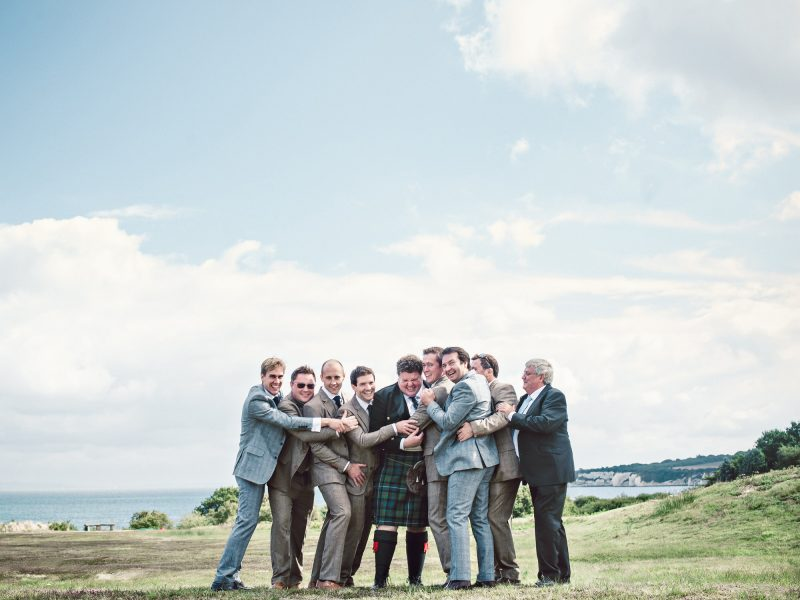 Relaxed fun full length portrait Groom Best Man and Ushers in tweed suits and a kilt hug the Groom with Studland Bay sea coastline in background Dorset