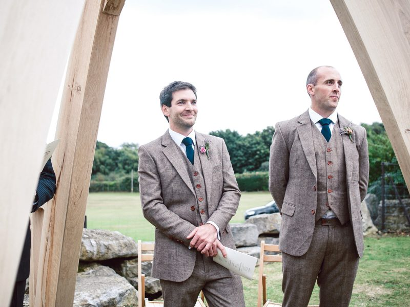 Emotional Groom and Best Man watch Bride walk down aisle for outdoor ceremony Studland Bay Dorset