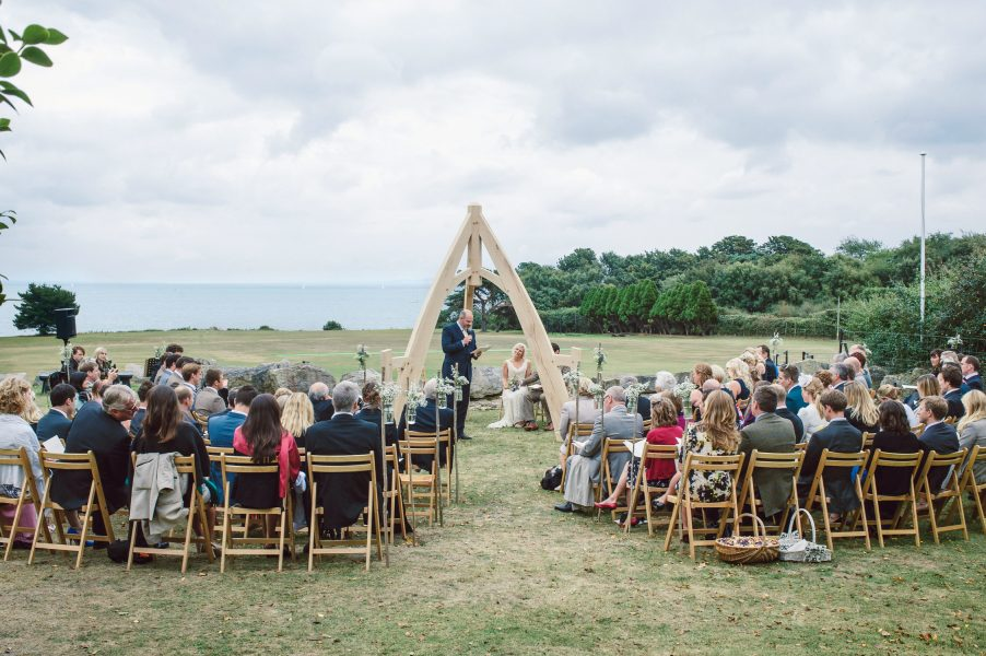Landscape view of the outdoor ceremony with wooden wedding arch framing Bride and Groom with sea in the background Studland Bay Dorset
