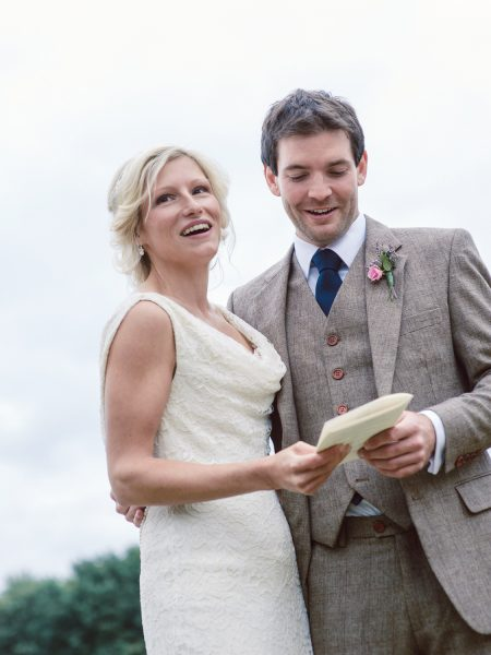 Bride and Groom read vows together for outdoor ceremony Studland Bay Dorset