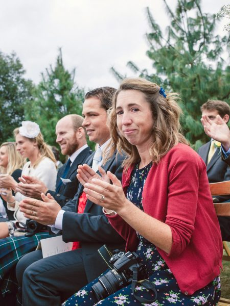 Emotional guests clap during the outdoor ceremony Studland Bay Dorset