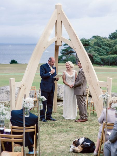 Bride and Groom take vows under wooden arch made by Groom while guests watch and dog sleeps Studland Bay Dorset