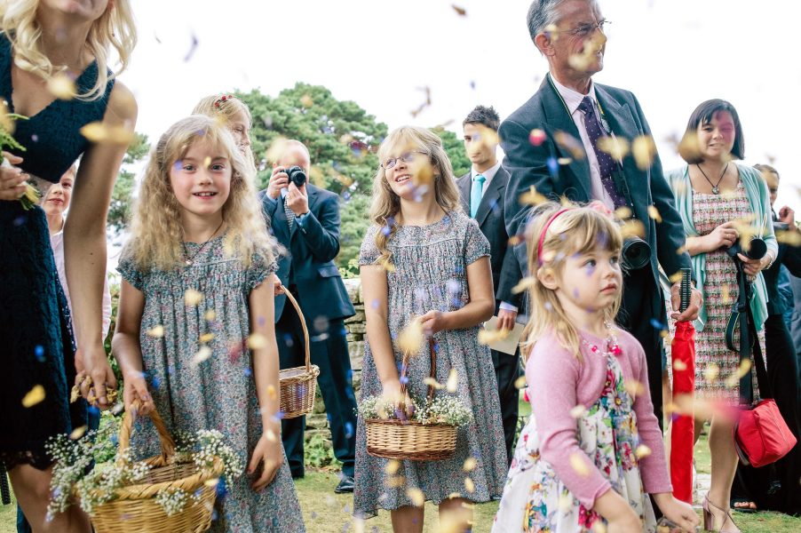 Rose petal Wedding confetti being thrown by flower girls in blue floral dresses Studland Bay Dorset