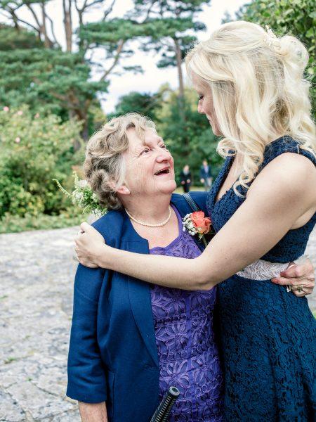Gran is hugged by Bridesmaid in navy dress Studland Bay Dorset