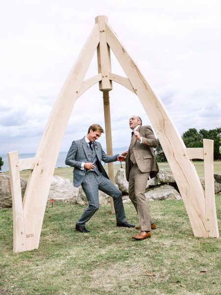 Ushers play air guitar under outdoor ceremony wooden Arch at Studland Bay Dorset