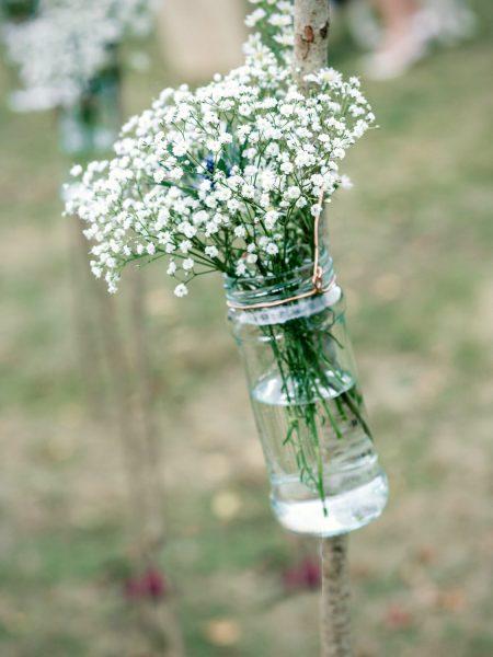 Rustic Gypsophila in mason jar lining aisle for outdoor wedding Studland Bay Dorset