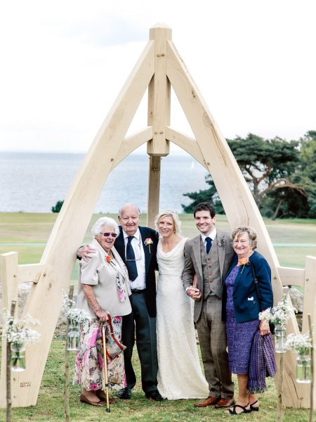 Family portrait under outdoor ceremony wooden Arch at Studland Bay Dorset with sea in background