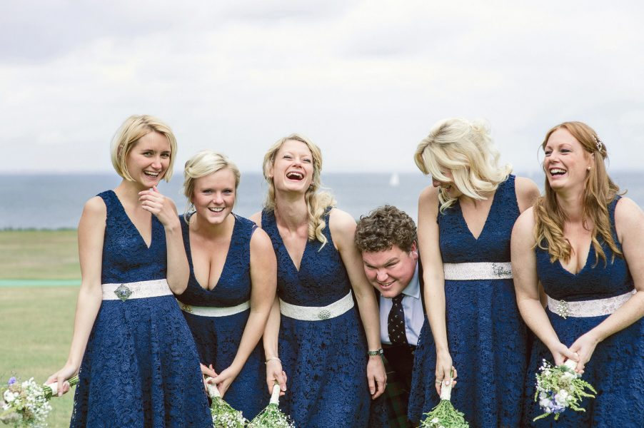 Bridesmaids in navy blue dresses giggle as an usher photo bombs the portrait Studland Bay Dorset with sea in background