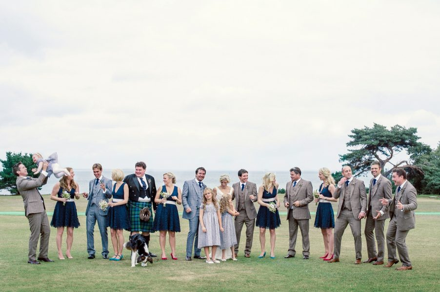 Relaxed fun Bridal party and dog portrait Studland Bay Dorset with sea in background