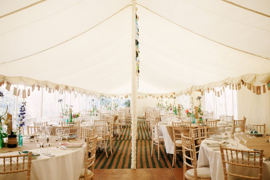 Marquee interior with homemade blue decorations and rustic touches Studland Bay Dorset