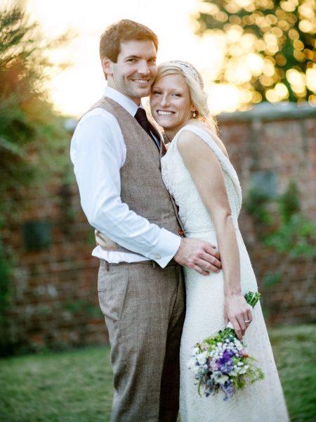 Bride in Charlie Breat dress holding wild meadow flower bouquet and Groom in brown tweed suit sunset portrait Studland Bay Dorset