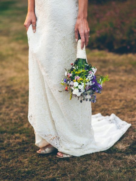 Portriat of bottom half of Bride's Charlie Brear dress and rustic wild meadow flower and hedgerow bouquet Studland Bay Dorset