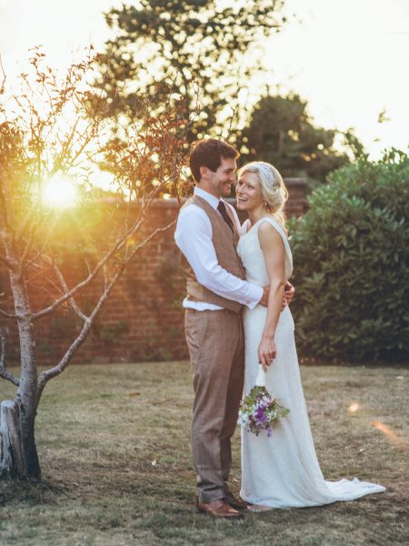 Bride in Charlie Breat dress holding wild meadow flower bouquet and Groom in brown tweed suit sunset portrait Studland Bay Dorset