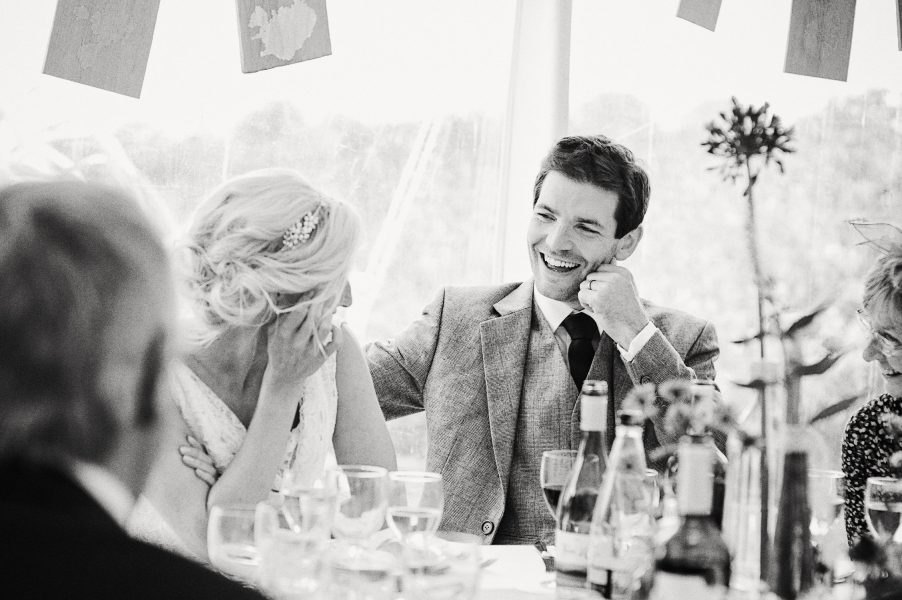 Groom laughs during wedding reception Studland Bay Dorset