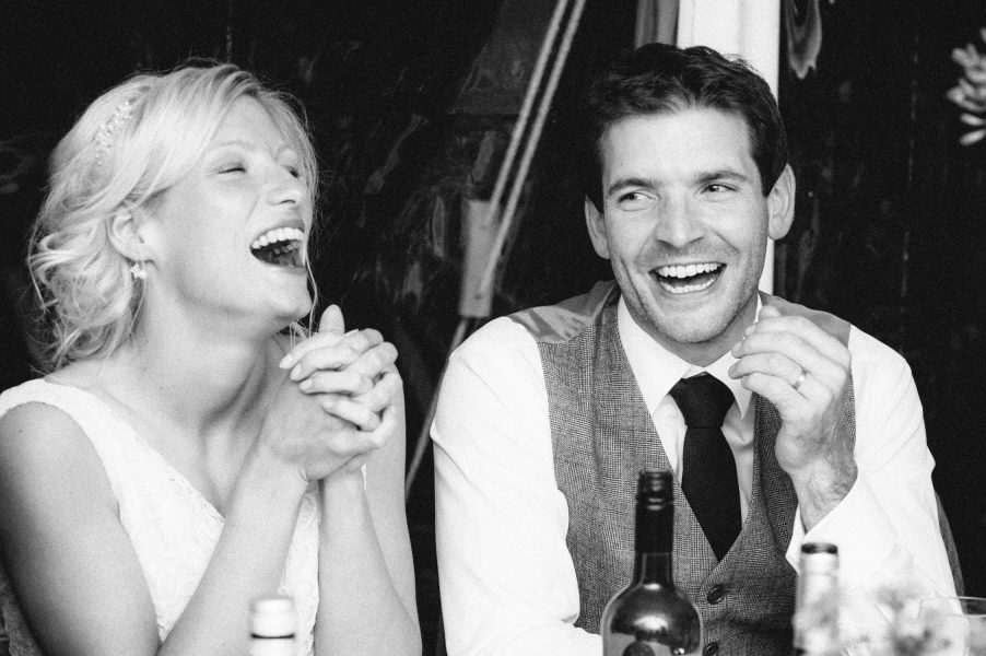 Bride and Groom laugh during wedding reception speeches Studland Bay Dorset