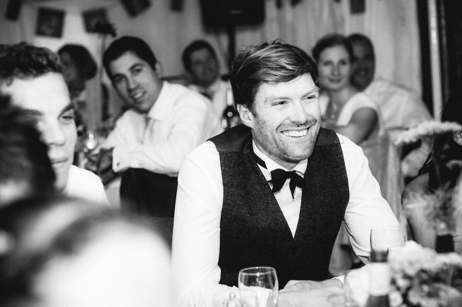 Wedding guest laughs during wedding reception speeches Studland Bay Dorset