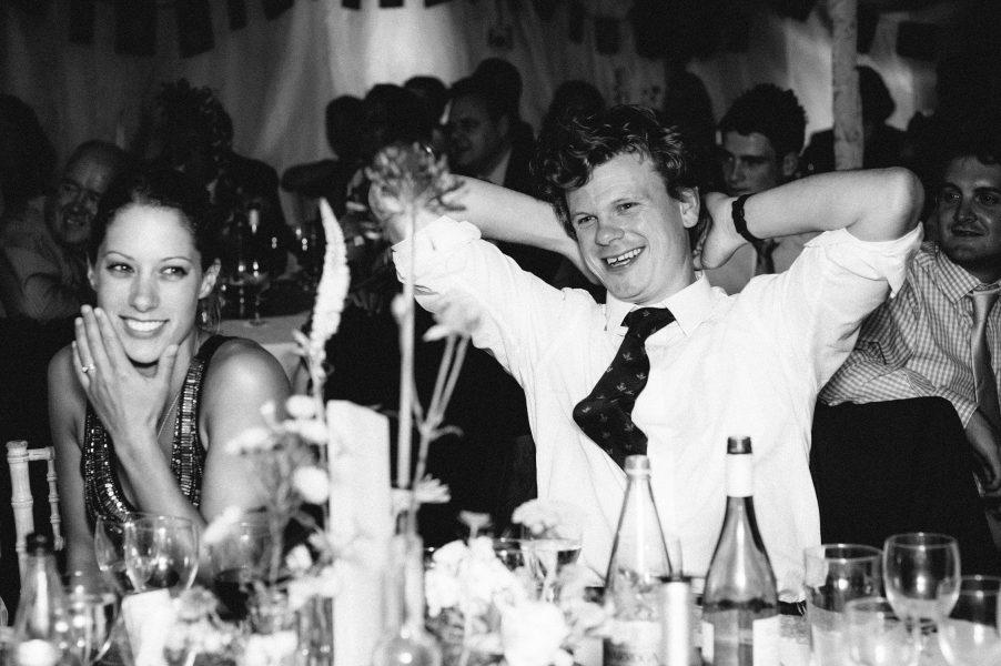 Wedding guests laugh during wedding reception speeches Studland Bay Dorset