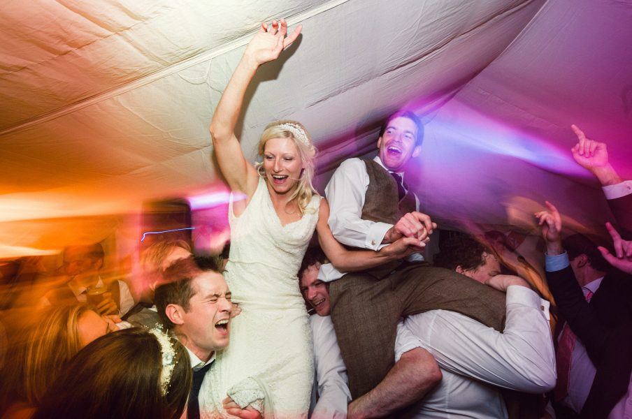 Bride and Groom raised in air sitting on guests shoulders as everyone cheers on animated energetic dance floor Studland Bay Dorset
