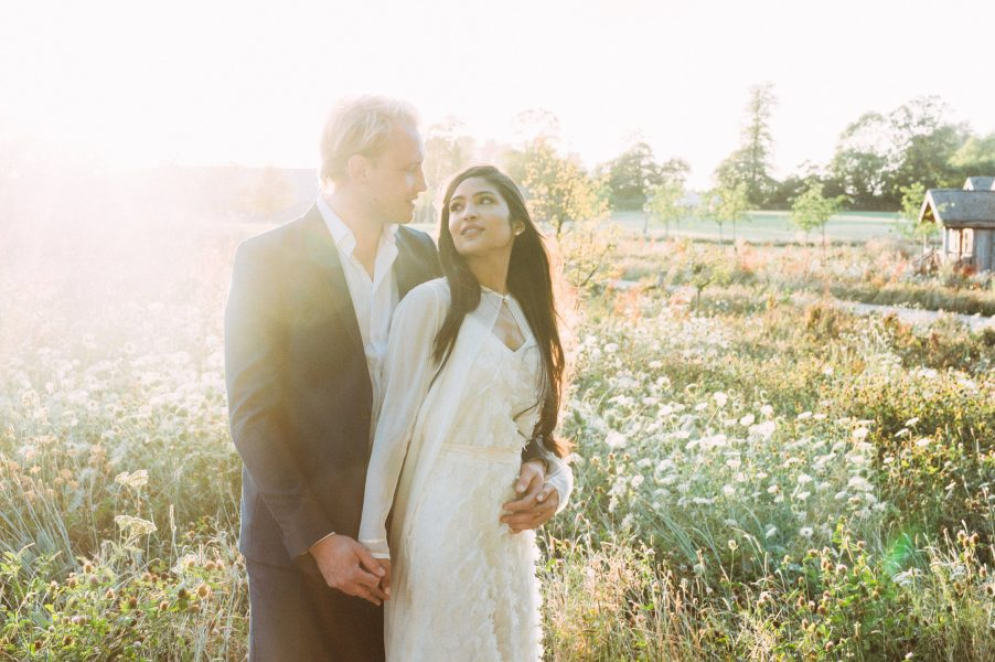 Dreamy wedding couple backlit in a summer meadow of flowers