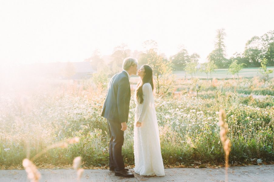 Dreamy wedding couple kiss in a backlit summer meadow of flowers