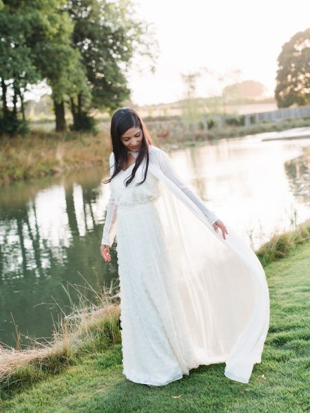 Boho bride with long hair down flowing dress in front of beautiful lake