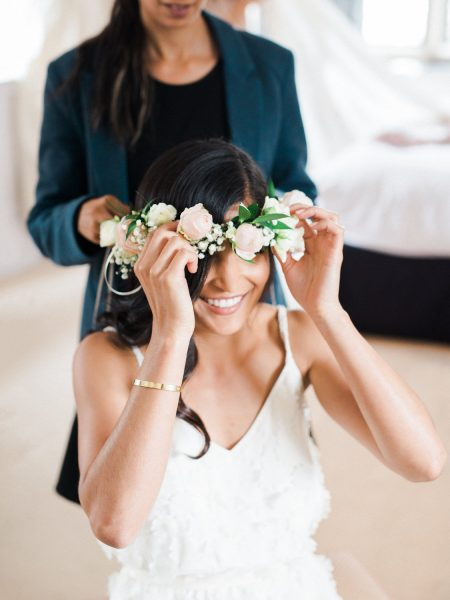 Bride putting on blush rose floral crown laughing
