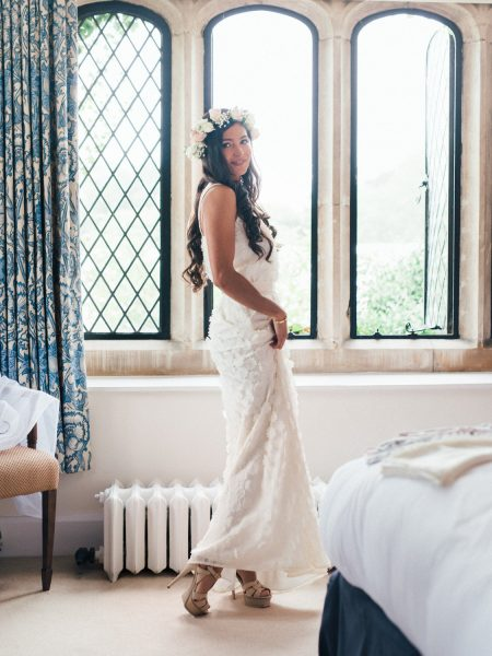 Full length portrait of Bride in floral crown in front of window