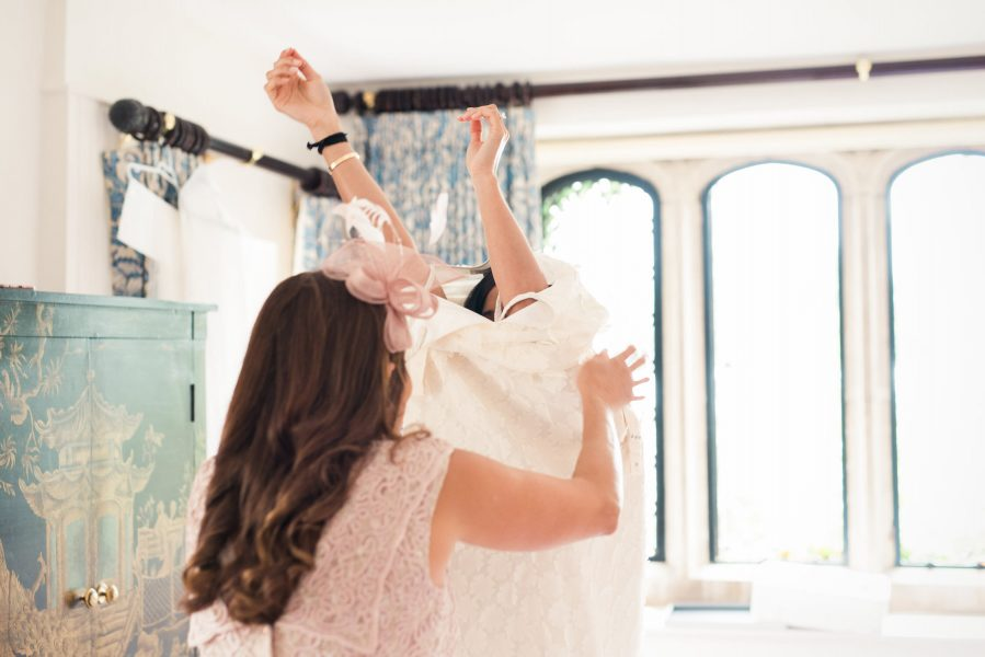 Bride putting on wedding dress helped by mother