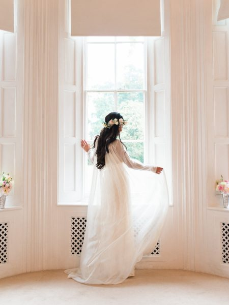 Boho bride luxe holding floaty wedding dress in front of window at Weston on the Green Oxfordshire