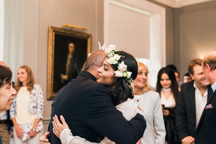 Bride in floral crown hugging father post ceremony