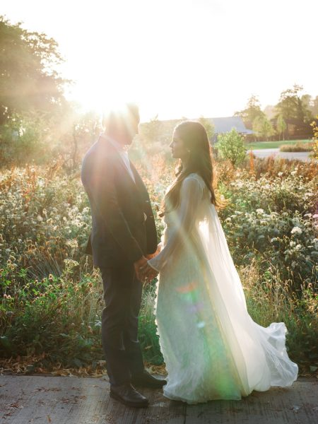 Bride and Groom backlit sunset portrait in front of glowing wild meadow Soho Farmhouse Oxfordshire