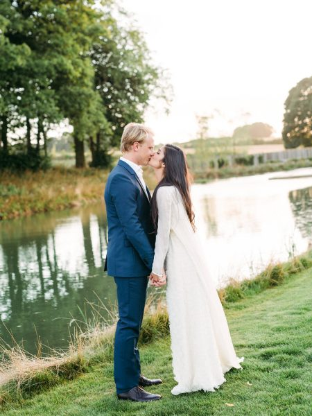 Bride and Groom kissing by a lake wedding portrait Soho Farmhouse Oxfordshire