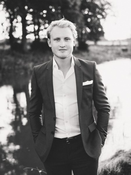 Black and white portrait of Groom standing in from of lake Soho Farmhouse Oxfordshire