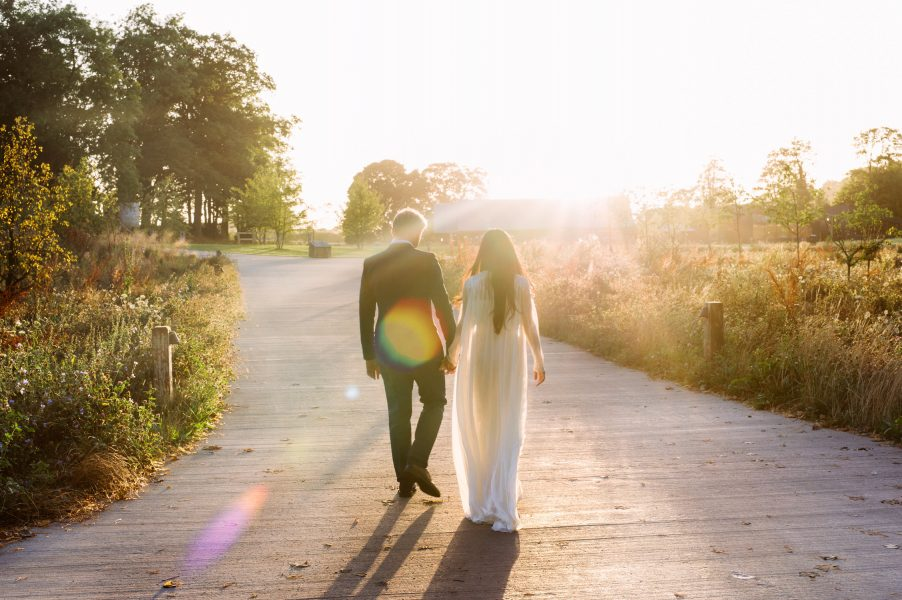Bride and Groom backlit portrait walking into the sunset with meadows either side Soho Farmhouse Oxfordshire