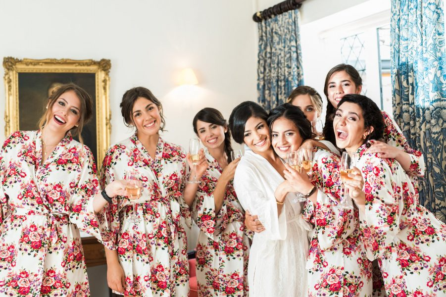 Bridal prep of Bride and her bridesmaids hugging and smiling in floral dressing gowns Weston on the Green Manor